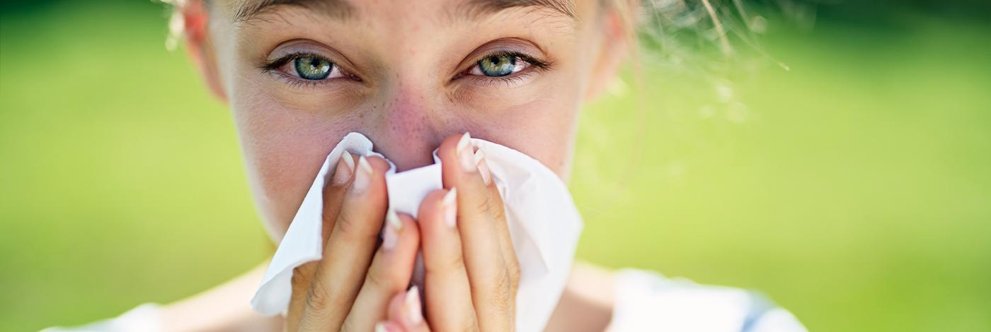 Allergisk jente som blåser seg i nesen.